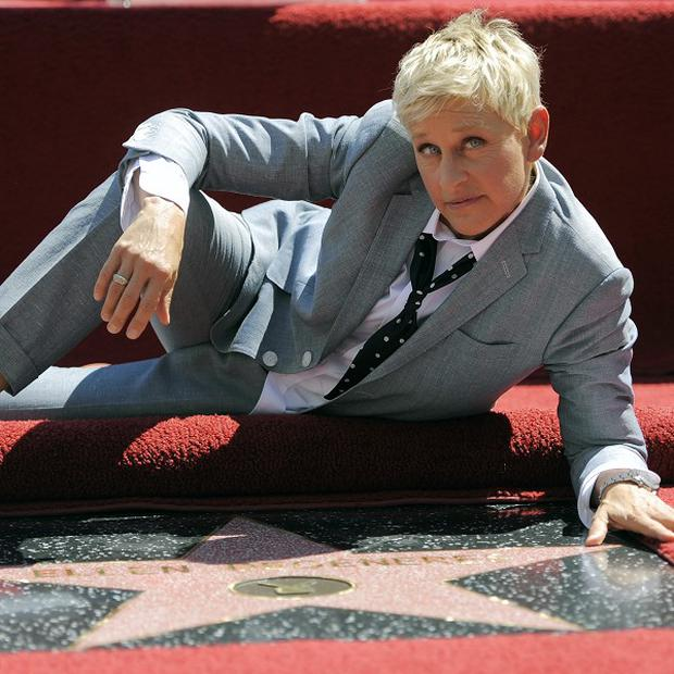 Ellen DeGeneres poses with her star on the Hollywood Walk of Fame