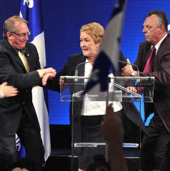 Parti Quebecois leader Pauline Marois is whisked off stage as she delivers her victory speech in Quebec (AP/Paul Chiasson, The Canadian Press)