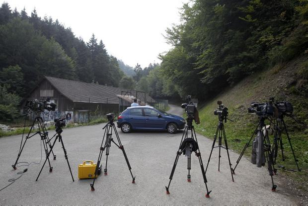 Cameras are seen in front of Gendarmes who blocks access to a site where people were shot to death near Chevaline, French Alps, Thursday Sept. 6, 2012. A 4-year-old British girl hid for eight hours beneath the bodies of slain family members in the back of their car before she was discovered by French investigators who had been guarding the vehicle, a prosecutor said Thursday. Three people - a man and two women - had been shot to death, as was a French cyclist whose body was found nearby