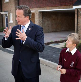 David Cameron is watched by nine-year-old Josh Wood during a visit to the Aldermere Housing development in Cheshunt, Hertfordshire