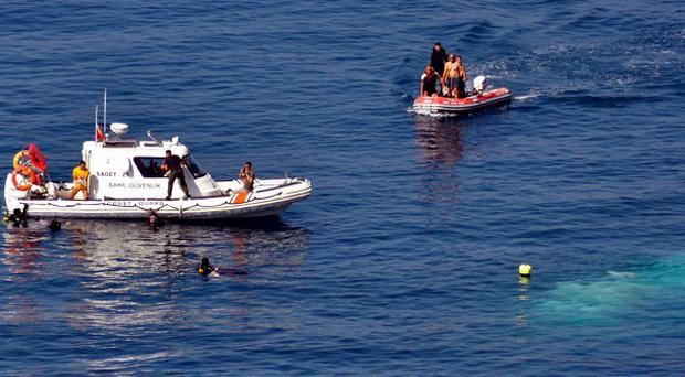 Coast guards search for survivors after at least 58 illegal immigrants drowned when a fishing boat sank after hitting rocks off the coast near Izmir, Turkey(AP Photo/Hurriyet)