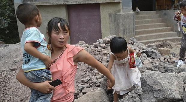 A woman guides children away from damaged buildings after an earthquake hit Luozehe town in Yiliang, China (AP)