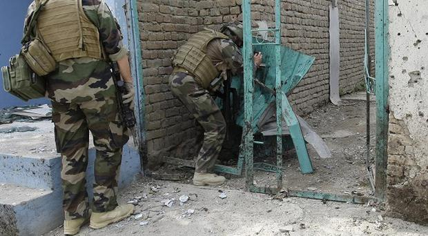 Nato soldiers inspect the scene of a suicide bomb attack in Kabul, Afghanistan (AP)