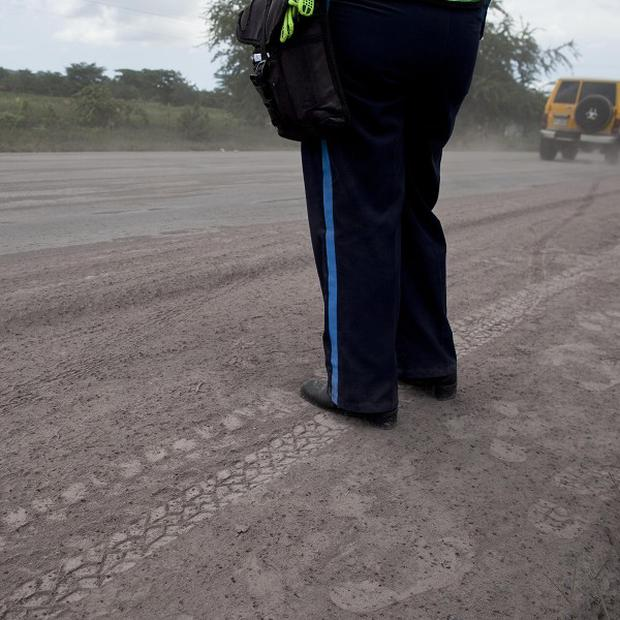 A police officer stands guard on a road blanketed with volcanic ash spewed from the San Cristobal volcano in Nicaragua (AP)