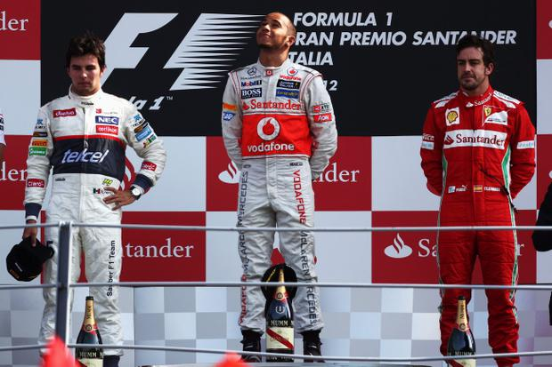 MONZA, ITALY - SEPTEMBER 09: Race winner Lewis Hamilton (C) of Great Britain and McLaren celebrates on the podium with second placed Sergio Perez (L) of Mexico and Sauber F1 and third placed Fernando Alonso (R) of Spain and Ferrari following the Italian Formula One Grand Prix at the Autodromo Nazionale di Monza on September 9, 2012 in Monza, Italy. (Photo by Andrew Hone/Getty Images)