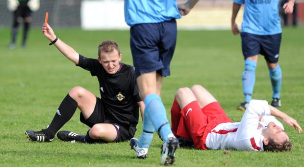 Referee Keith Kennedy grimaces in pain from an ankle injury he incurred as he rushed to give Ards Rangers' Jamie Patterson the red card for his challenge on Ards' Kyle McDowell. The referee was unable to continue due to his injury and the match was therefore abandoned