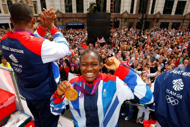 Boxer Nicola Adams holds her gold medal as she takes part in a parade through London, celebrating Britain's Olympic and Paralympic sporting heroes