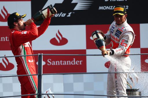 MONZA, ITALY - SEPTEMBER 09: Race winner Lewis Hamilton (R) of Great Britain and McLaren celebrates on the podium with third placed Fernando Alonso (L) of Spain and Ferrari following the Italian Formula One Grand Prix at the Autodromo Nazionale di Monza on September 9, 2012 in Monza, Italy. (Photo by Andrew Hone/Getty Images)