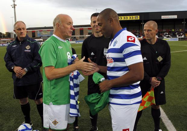 Northern Ireland legend Sammy McIlroy with QPR legend Les Ferdinand swap number 5 shirts before Monday night's Alan McDonald Memorial match at Seaview