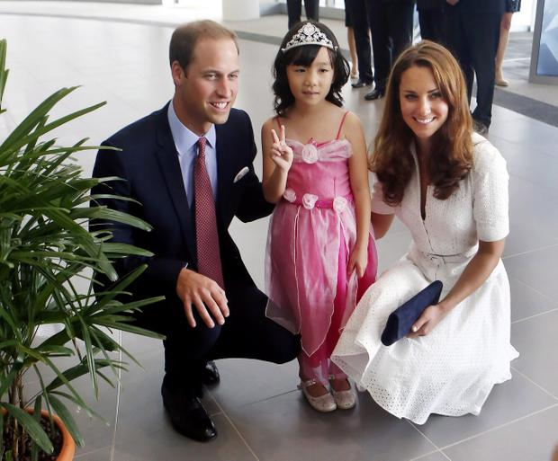 Prince William, Duke of Cambridge (L) and Catherine, Duchess of Cambridge (R) pose with four-year-old Maeve Low as they tour the Rolls-Royce Seletar Campus during the Diamond Jubilee tour at Seletar Aerospace Park on September 12, 2012 in Singapore.