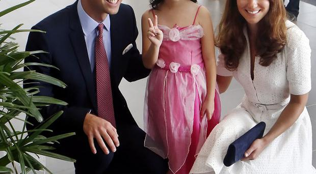The Duke and Duchess of Cambridge meet four-year-old Maeve Low during a visit to a Rolls-Royce factory in Singapore