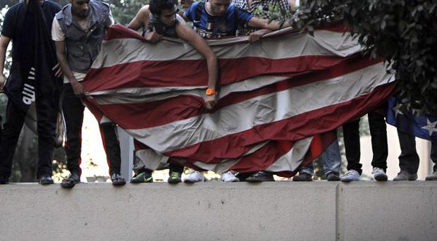 Egyptian protesters standing on the sidewall of the US embassy with an American flag pulled down from the embassy in Cairo, Egypt (AP/Nasser Nasser)
