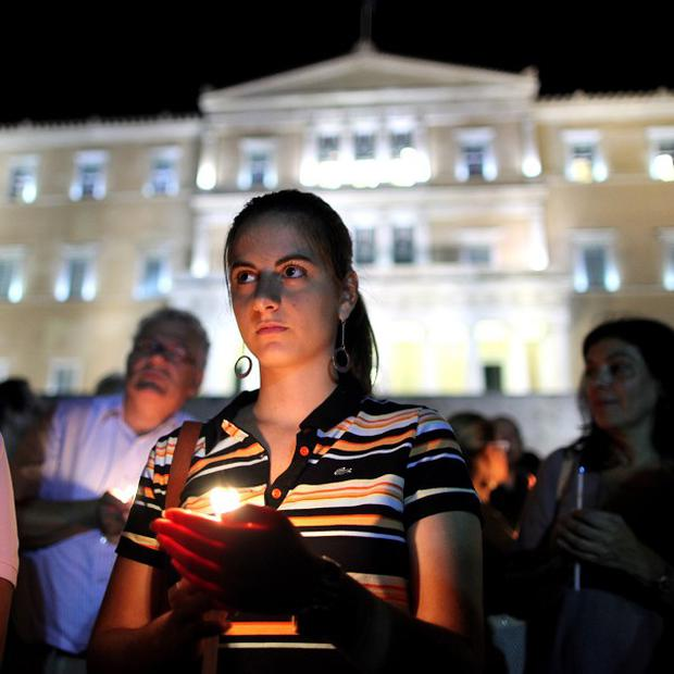 Protesters hold candles outside the Greek parliament during a demonstration by college and university professors against new cuts (AP)