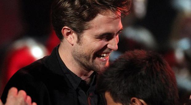 Robert Pattinson will walk the red carpet with Kristen Stewart at the Twilight premieres, it has been reported