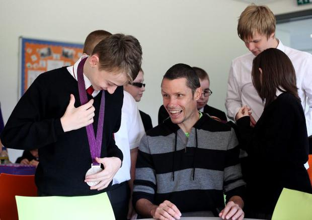 Kevin Curran tries on one of Jason Dunkerley's medals yesterday. The Canadian Paralympian bronze and silver medal winner was on a visit to Jordanstown School, where he was a pupil before emigrating to North America with his family at the age of 13