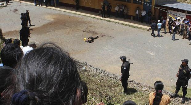 People look at the body of a man who was lynched by a mob inside a school in San Juan Tactic, Guatemala (AP)