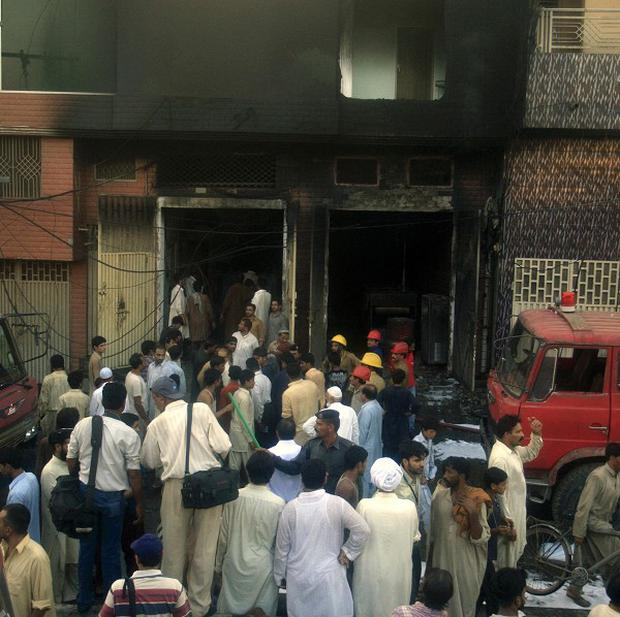People stand outside a factory after a fatal fire in Lahore, Pakistan (AP)