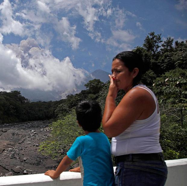 A boy watches plumes of smoke and volcanic ash rise from the Volcan de Fuego as seen from Palin, south of Guatemala City (AP/Moises Castillo)