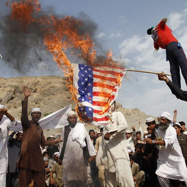 Afghans burn the US flag in Nangarhar province during a protest against an anti-Islam film (AP)