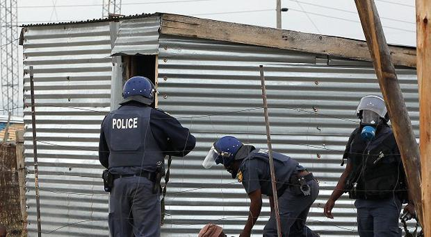 Police officers round up a group of men near the Lonmin Platinum Mine near Rustenburg, South Africa (AP/Themba Hadebe)
