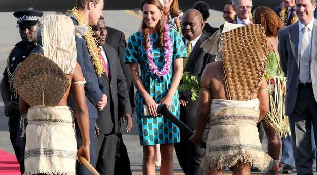 HONIARA, GUADALCANAL ISLAND, SOLOMON ISLANDS - SEPTEMBER 16: Prince William, Duke of Cambridge and Catherine, Duchess of Cambridge twatch traditional dancing as they arrive at Honiara International Airport during their Diamond Jubilee tour of the Far East on September 16, 2012 in Honiara, Guadalcanal Island. Prince William, Duke of Cambridge and Catherine, Duchess of Cambridge are on a Diamond Jubilee tour representing the Queen taking in Singapore, Malaysia, the Solomon Islands and Tuvalu. (Photo by Chris Jackson/Getty Images)