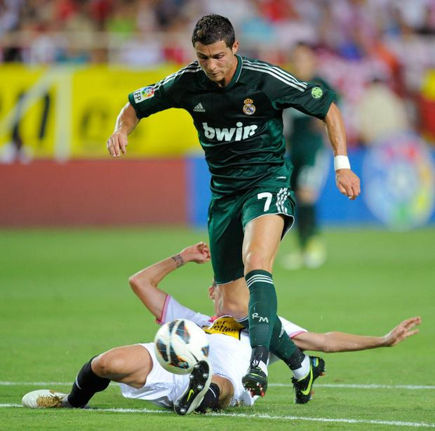 SEVILLE, SPAIN - SEPTEMBER 15: Cristiano Ronaldo (#7) of Real Madrid CF is tackled by Fernando Navarro of Sevilla FC during the La Liga match between Sevilla FC and Real Madrid at Estadio Ramon Sanchez Pizjuan on September 15, 2012 in Seville, Spain. (Photo by Denis Doyle/Getty Images)
