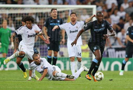 MADRID, SPAIN - SEPTEMBER 18: Yaya Toure of Manchester City FC beats Pepe of Real Madrid on his way to setting up the first goal during the UEFA Champions League Group D match between Real Madrid and Manchester City FC at Estadio Santiago Bernabeu on September 18, 2012 in Madrid, Spain. (Photo by Alex Livesey/Getty Images)