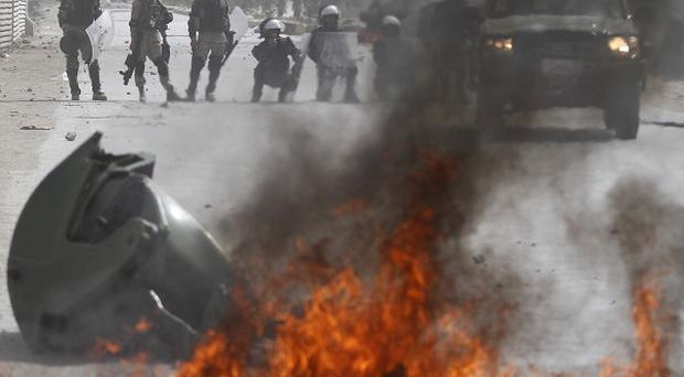 Afghan police stand by burning tyres during a protest, in Kabul (AP)