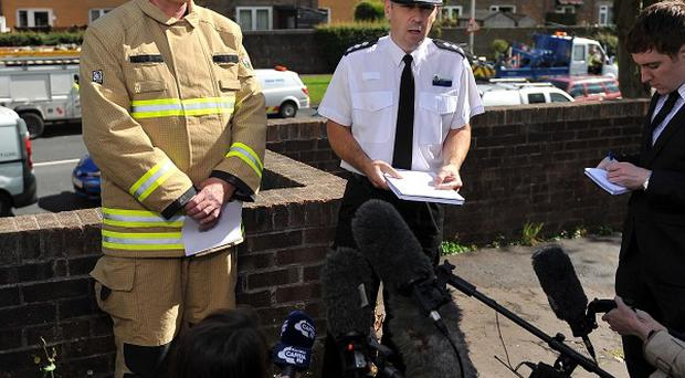 Fire and police officers speak to the media outside the property in Cwmbran where three people died