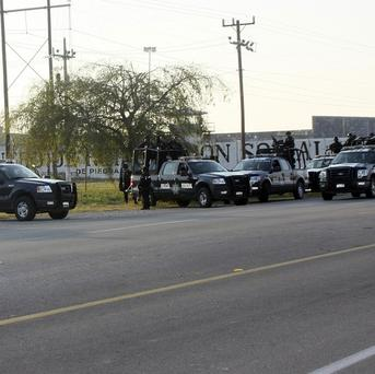 Federal police stand guard outside the prison in Piedras Negras, Mexico, where dozens of prisoners escapaed from