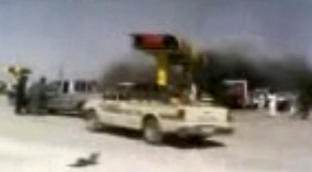 People are seen after an airstrike on a gas station in Raqqa, Syria (AP/Ugarit News via AP video)