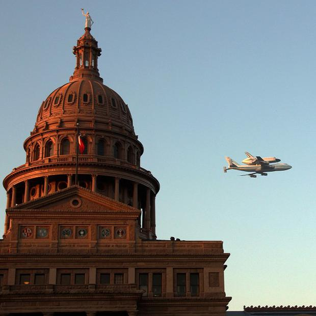 Space shuttle Endeavour sits atop the shuttle aircraft carrier as it flies over Austin, Texas (AP)