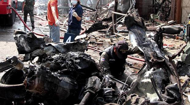 Thai police examine the wreckage of a pickup truck after a bomb hidden in it exploded killing five people (AP)