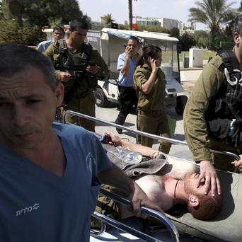 An injured Israeli soldier is wheeled into Soroka hospital in the southern town of Beersheva after the gun battle(AP)