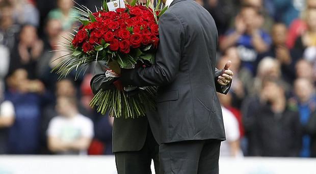 Sir Bobby Charlton (left) passes flowers to Ian Rush on the pitch prior to kick-off