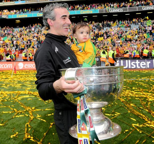 Party on: Jim McGuinness marks the win with his son Jim Jr and the Sam Maguire