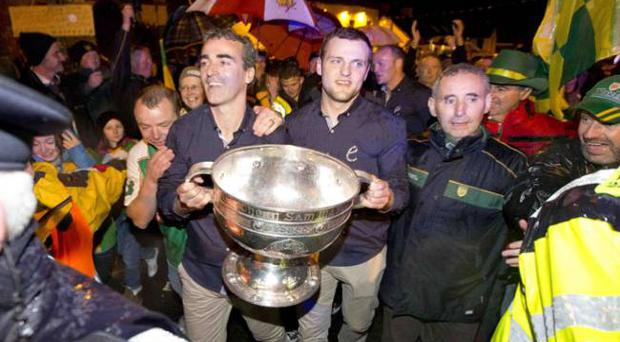 GAA Football All Ireland Champions Donegal Homecoming, Pettigo. Donegal manager Jim McGuinness and captain Michael Murphy carry the Sam Maguire across the Termon river from Co Fermanagh into Co Donegal