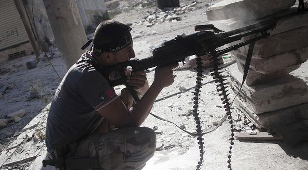 A Free Syrian army fighter fires at Syrian army positions during clashes (AP)