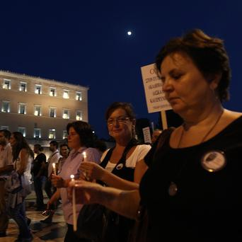 Protesters hold candles outside the Greek parliament during a demonstration by college and university professors in Athens (AP)