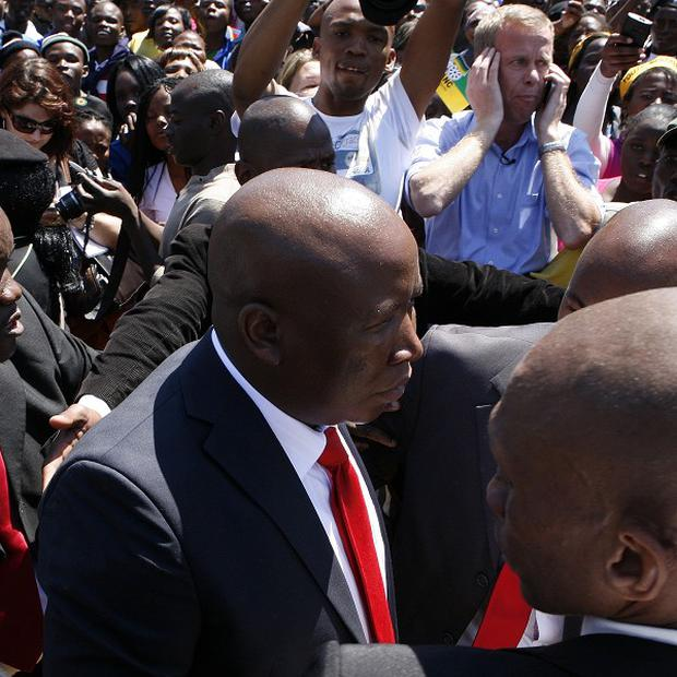 Julius Malema enters court escorted by bodyguards (AP)