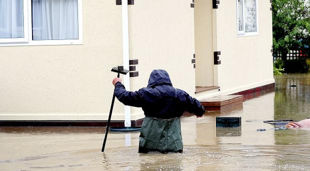 A resident of Knaresborough wades through water following flooding from the River Nidd in the North Yorkshire town