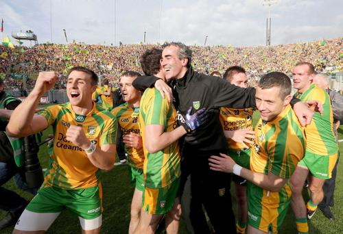 Donegal manager Jim McGuinness celebrates on the Croke Park pitch with his team at the end of the 2012 All Ireland final