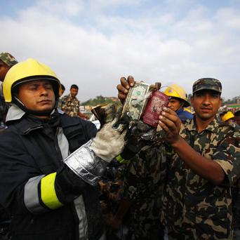 A Nepalese soldier and firefighter display a British passport and some US dollars found at the aircraft crash site in Nepal (AP)