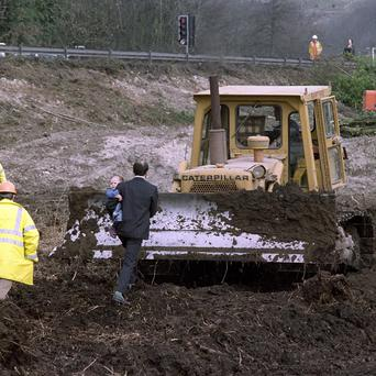A protester pictured in March 1992 carrying a young child steps in front of a bulldozer to oppose the M3 extension at Twyford Down in Hampshire (PA)