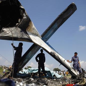 Nepalese police inspect the wreckage of a Sita Air plane at the crash site near Katmandu (AP)
