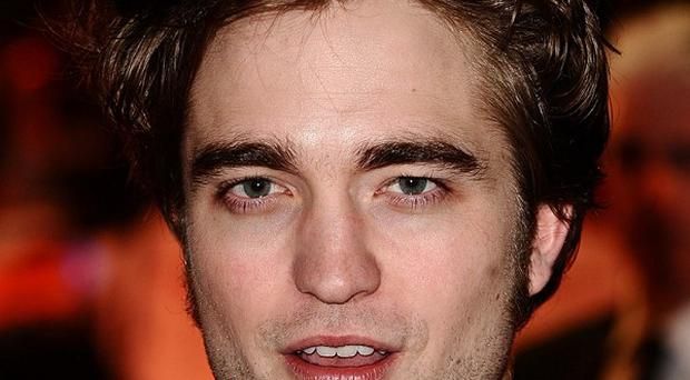 Twilight star Robert Pattinson has maintained his place as the world's sexiest man in the Glamour poll