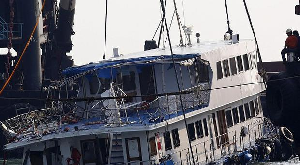 A half submerged boat is lifted out of the water after Monday night's fatal collision near Lamma Island, off the southwestern coast of Hong Kong (AP)