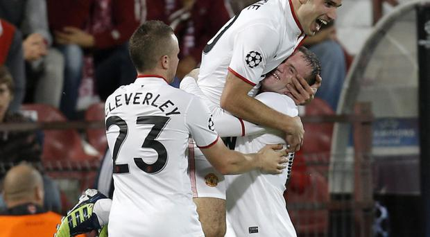 Manchester United's Robin van Persie, top, celebrates with Wayne Rooney, right, after scoring his second goal against CFR Cluj in Cluj, Romania, Tuesday, Oct. 2, 2012, during an UEFA Champions League, Group H, soccer match.(AP Photo/Vadim Ghirda)