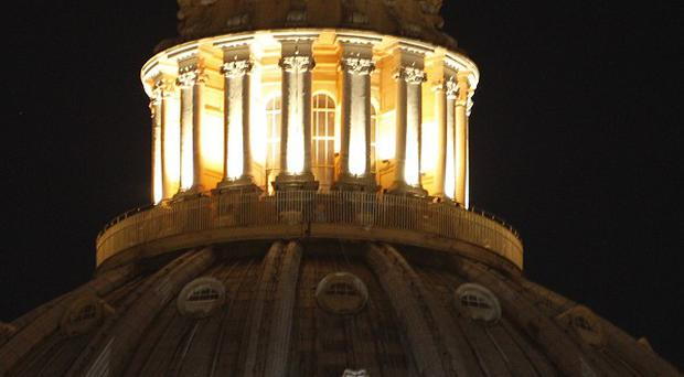 A banner hangs from a window of St Peter's dome in protest over Italian premier Mario Monti (AP)