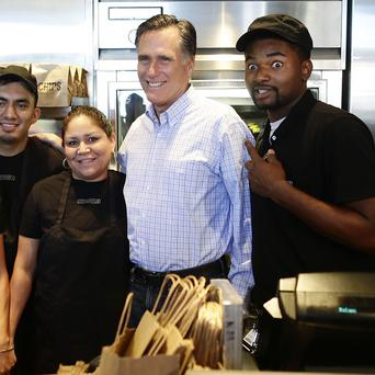 Republican presidential candidate Mitt Romney poses with workers at a Chipotle restaurant in Denver (AP)